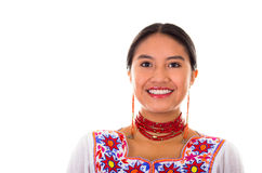 Charming young woman wearing traditional andean blouse with colorful embroideries, matching red necklace and earrings Stock Photo