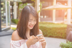 Charming young woman in white shirt reads or texts message to mobile phone. Charming young woman in white shirt reads or texts message to mobile phone, against Royalty Free Stock Photography