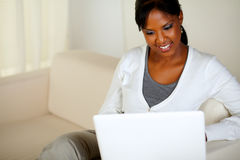 Charming young woman working on laptop. Portrait of a charming young woman working on laptop while sitting on sofa Royalty Free Stock Photo