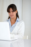 Charming young woman working on laptop computer Royalty Free Stock Photography