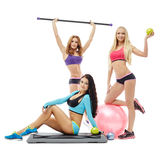 Charming young women posing with sports equipment Royalty Free Stock Photos