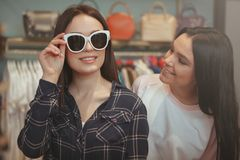 Charming young women shopping for eyewear. Beautiful women smiling, trying on new sunglasses, shile shopping with her best friend. Two lovely young women royalty free stock photography