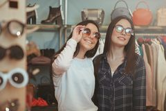 Charming young women shopping for eyewear. Two lovely cheerful female friends trying on sunglasses, while shopping together at clothing store. Beautiful women royalty free stock photos