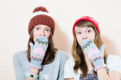 2 charming young women in winter caps gloves puzzled looking in camera on white background portrait. Two funny charming young women in winter caps gloves puzzled Stock Photo