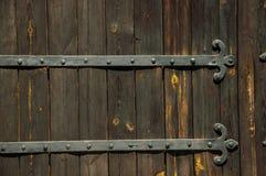 Charnière de fer travaillé avec des goujons dans une vieille porte en bois photos libres de droits
