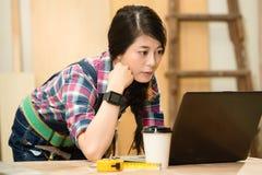 Charpentier à l'aide de l'ordinateur portable avec le smartwatch images libres de droits
