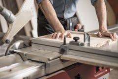 Charpentier à l'aide de la machine de sawing Images libres de droits