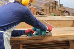 Charpentier à l'aide de la planeuse électrique avec la planche en bois dans l'atelier de menuiserie Images stock