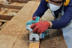 Charpentier à l'aide de la planeuse électrique avec la planche en bois dans l'atelier de menuiserie Il utilise le dispositif de p Photographie stock