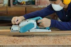 Charpentier à l'aide de la planeuse électrique avec la planche en bois dans l'atelier de menuiserie Il utilise le dispositif de p Image stock