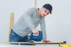 Charpentier à l'aide de la scie électrique pour couper le bois Photographie stock
