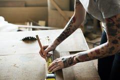 Charpentier à l'aide du crayon et de la bande de mesure sur le bois photos stock