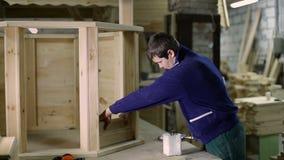 Charpentier appliquant la colle sur la planche en bois avec la brosse banque de vidéos
