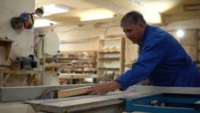 Charpentier au travail à son atelier, traitement de bois sur une machine de travail du bois banque de vidéos