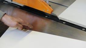 Charpentier coupant la feuille de carton gris banque de vidéos
