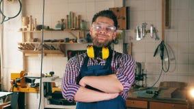 Charpentier dans l'atelier de menuiserie Un homme dans les vêtements de travail sourit tout en étant à la menuiserie banque de vidéos