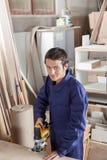 Charpentier dans son atelier avec une scie électrique Images libres de droits
