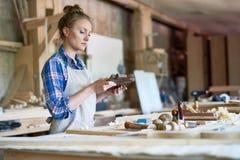 Charpentier féminin Holding Wooden Part dans l'atelier images stock
