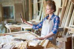 Charpentier féminin Making Wooden Parts dans l'atelier photos stock