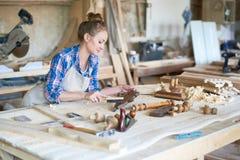 Charpentier féminin Polishing Wooden Part dans l'atelier photographie stock libre de droits