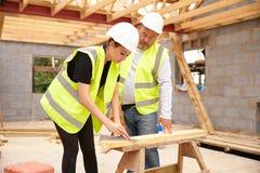 Charpentier With Female Apprentice travaillant au chantier image stock