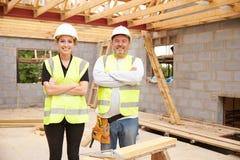 Charpentier With Female Apprentice travaillant au chantier images libres de droits