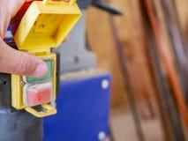 Charpentier mettant en marche la machine de rabotage dans un petit atelier image stock
