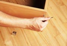 Charpentier montant les meubles en bois images stock