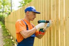 Charpentier prêt à tournoyer la vis dans la barrière en bois Photo libre de droits