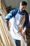 Charpentier qualifié Choosing Wooden Boards de stockage images libres de droits