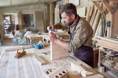 Charpentier qualifié Sanding Wooden Park dans l'atelier photographie stock libre de droits