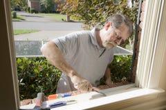 Charpentier réparant le châssis de fenêtre images libres de droits