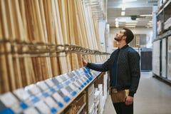 Charpentier sélectionnant le bois dans un magasin de matériel image libre de droits