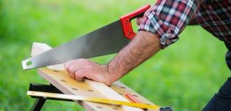Charpentier sciant une place en bois avec une scie en bois Photographie stock libre de droits
