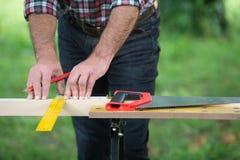 Charpentier sciant une place en bois avec une scie en bois Photo stock
