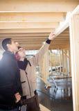 Charpentier Showing Wooden Roof au collègue au site photographie stock libre de droits