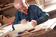 Charpentier supérieur envoyant le morceau de bois de construction avec le papier sablé Image stock
