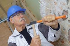 Charpentier supérieur travaillant avec le marteau et le burin Photo stock