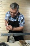 Charpentier supérieur travaillant dans son atelier Photos libres de droits