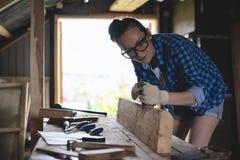Charpentier surfaçant un faisceau en bois avec une planeuse de main dans l'atelier images libres de droits
