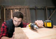 Charpentier, travail du bois de travailleur mesurant, forant et faisant le produit de bois de construction photo stock