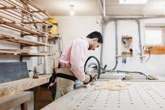 Charpentier travaillant avec l'avion et la planche en bois ? l'atelier photo libre de droits