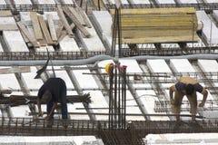 Charpentiers au travail dans le chantier de construction préparant des renforts Photo stock