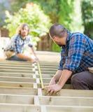 Charpentiers mesurant le bois avec la bande au site images libres de droits