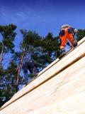 Charpentiers sur un toit en bois Image libre de droits