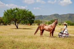 Charra med hennes häst på ett gräsfält Arkivbild