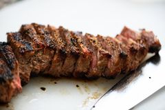 Charred beef and knife blade. Charred beef sliced with seasoning and knife blade next to it royalty free stock image