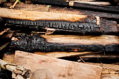 The charred boards lie on a pile. Many old boards stock photos