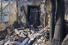 The charred entrance door. In a wall of the ownerless house after a fire Stock Photos