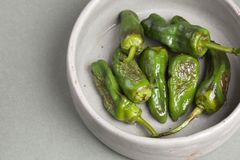 Charred green chillies in a pottery bowl. Seven charred green chillies in a light grey pottery bowl on a green surface royalty free stock photography